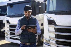 Homem clicando na tela de um tablet em uma garagem de caminhões.